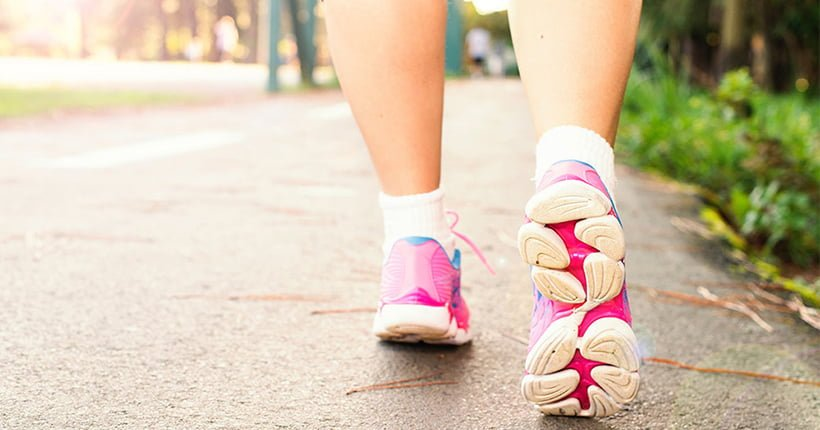 Close up of a woman walking in pink running shoes