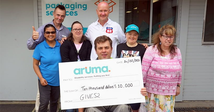 Aruma employees and customers holding a cheque from Give52