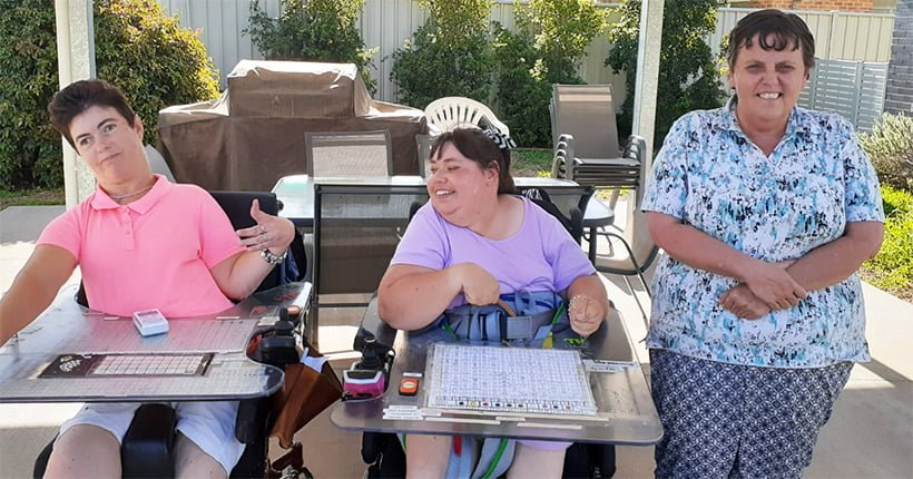 Three women with a disability in a courtyard outside. Two use a wheelchair.