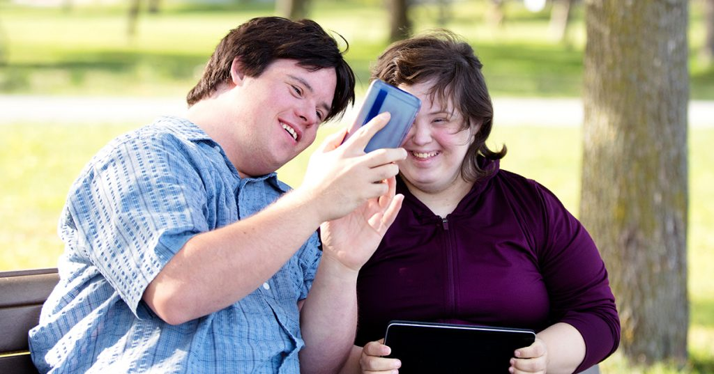 Couple with Down Syndrome in a park with mobile phone.