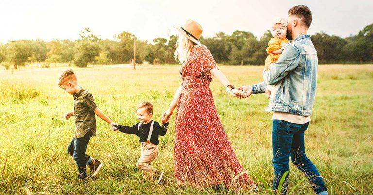 Family walking through a farm holding hands