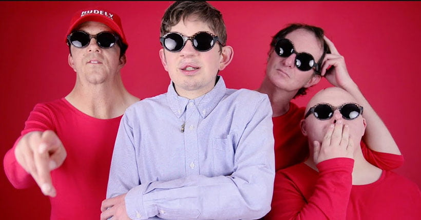 Members of Rudely interrupted in front of a red background