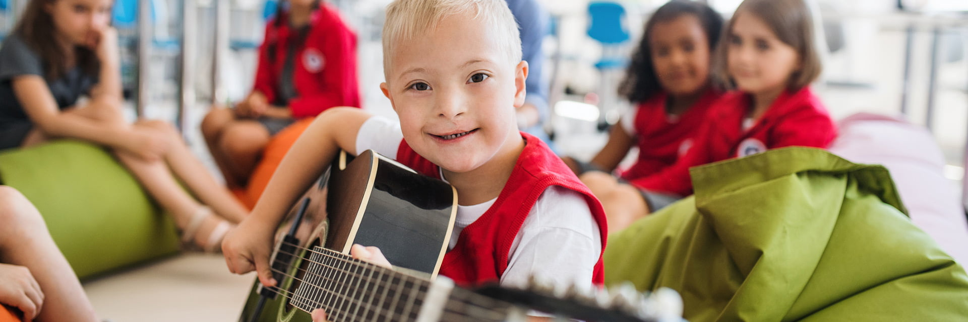 Young boy with a disability playing a guitar