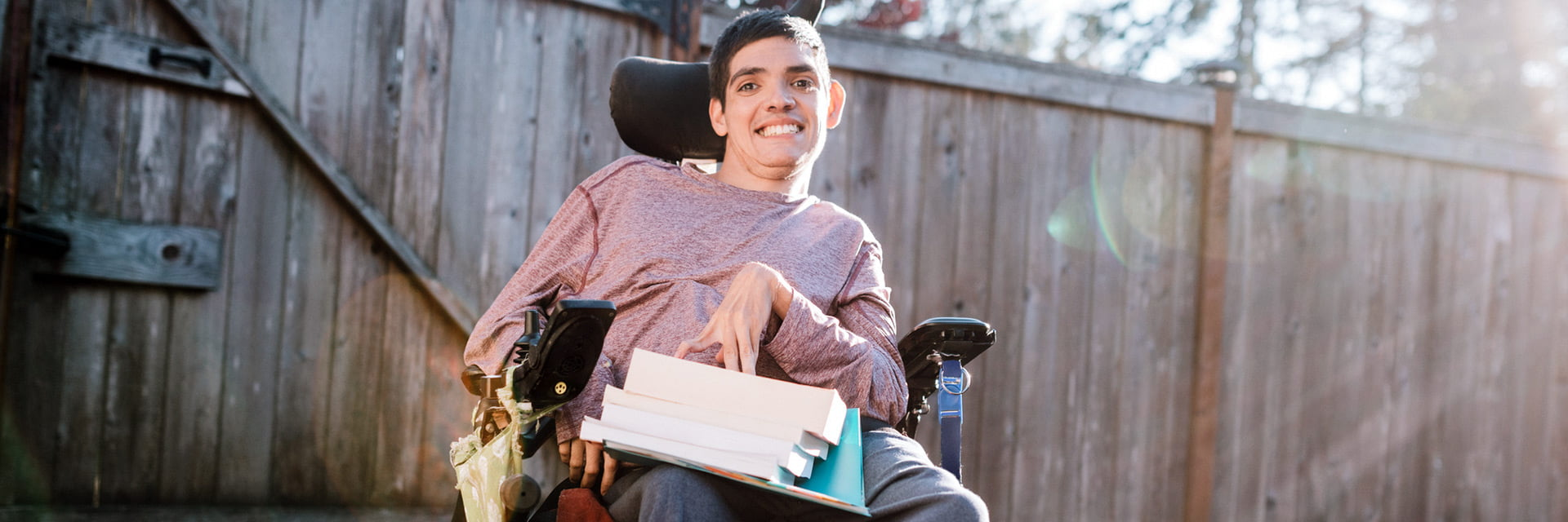 Man with a disability using a wheelchair outside with a stack of books on his lap