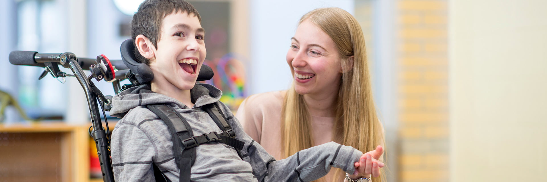Child with a disability using a wheelchair with a female carer