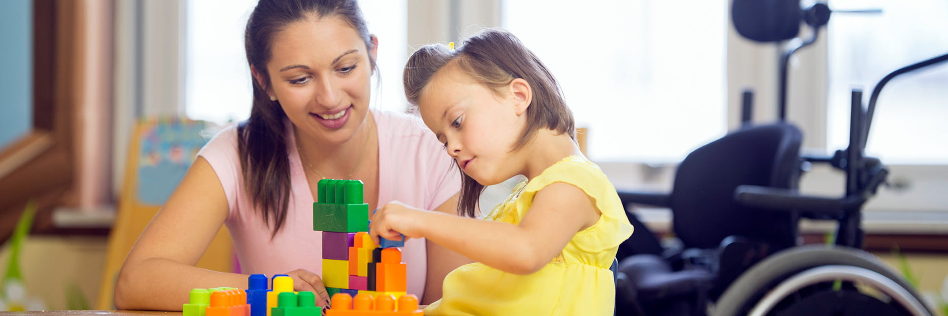 Support Worker and child with a disability playing with building blocks together