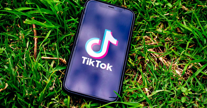 A mobile phone on the grass with the TikTok app on the screen