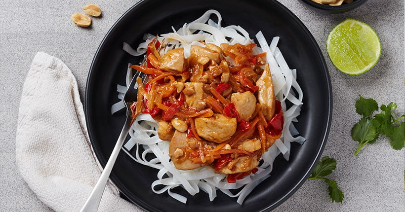 A bowl of pad Thai on a grey bench