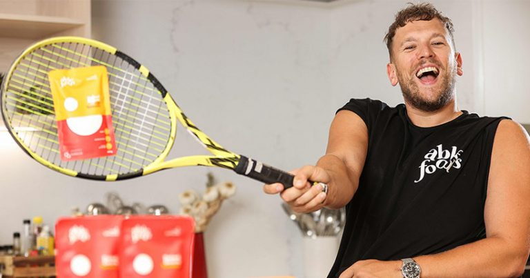 Dylan Alcott hitting a packet of baked beans with a tennis racquet