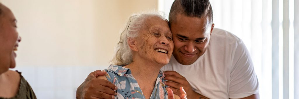 A man hugging an older women, both are smiling