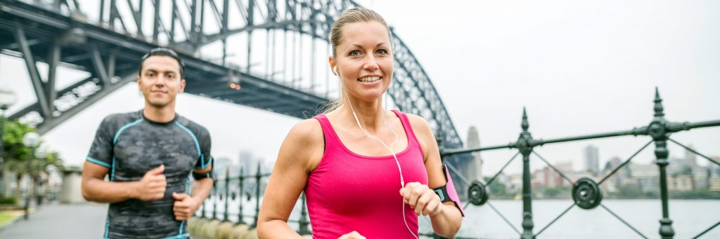 Woman wearing a pink top running with a man in a grey top near the Sydney Harbour Bridge