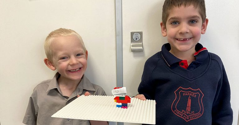Two young boys smiling, holding up LEGO