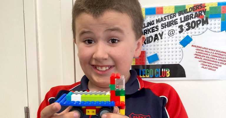 A young boy holds up a LEGO with an excited smile